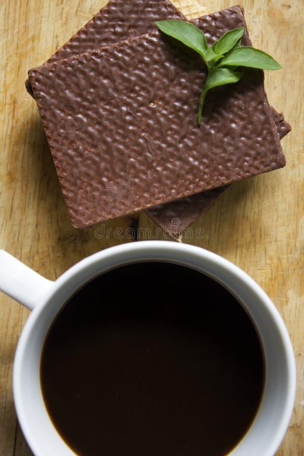 Μαύρος καφές στην άσπρη σοκολάτα γυαλιού και γκοφρετών στοκ φωτογραφίες