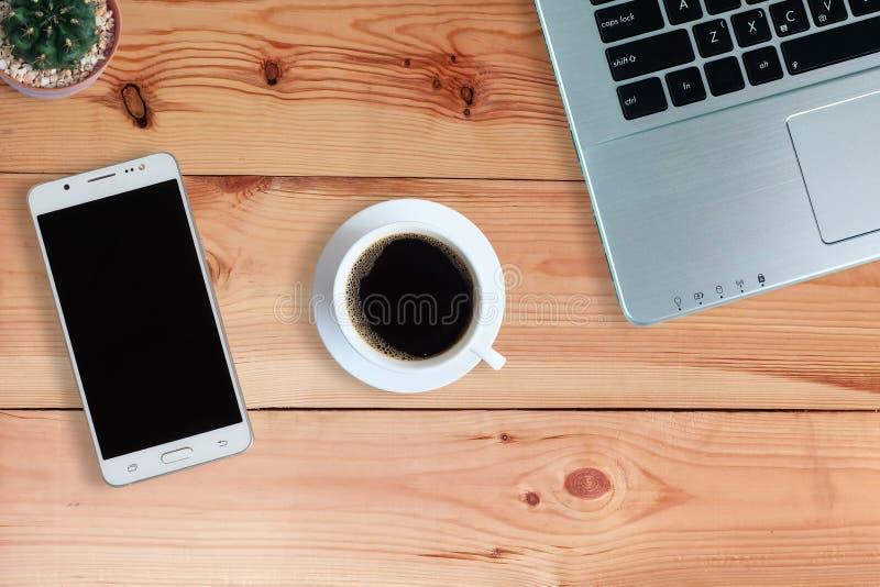 Μαύρος καφές στο άσπρο φλυτζάνι και το φορητό προσωπικό υπολογιστή και τον κάκτο και το κινητό τηλέφωνο ή Smartphone με την κενή  στοκ εικόνες