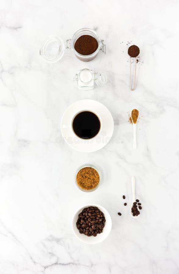 Μαύρος καφές στο φλυτζάνι, τη ζάχαρη, τον επίγειο καφέ και τα φασόλια στοκ φωτογραφία με δικαίωμα ελεύθερης χρήσης