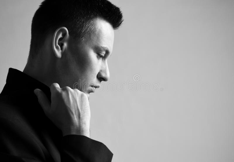 Μαύρος-λευκό portrair του στοχαστικού σύγχρονου ατόμου που στέκεται λοξά και που ανατρέχει κάτω από turnes το περιλαίμιο του σακα στοκ εικόνες