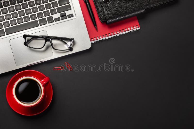 Μαύρος πίνακας γραφείων γραφείων με τον κενό φορητό προσωπικό υπολογιστή οθόνης, το σημειωματάριο, το ποντίκι, το φλιτζάνι του κα στοκ εικόνα