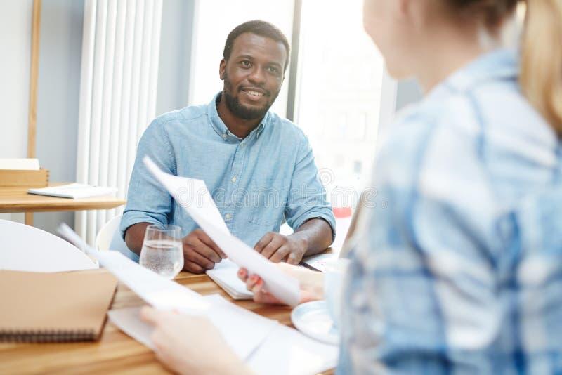 Μαύρος που εξετάζει τον ανώνυμο συνάδελφο στοκ εικόνες