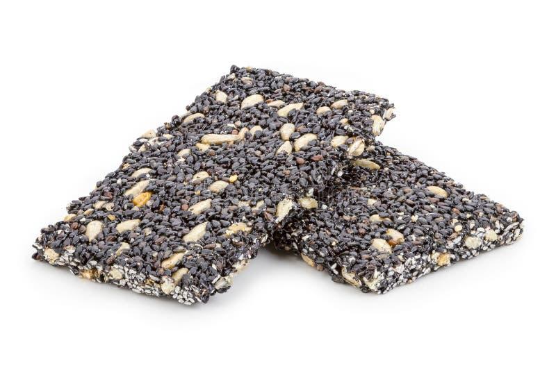 Μαύρος φραγμός σουσαμιού φραγμών Granola στο άσπρο υπόβαθρο στοκ εικόνα