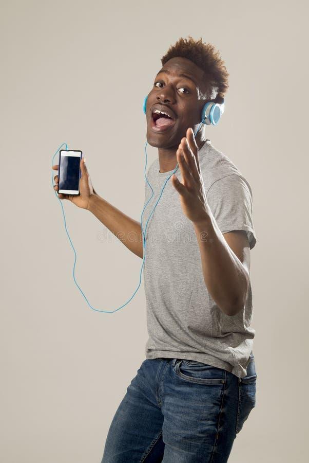 Μαύρο άτομο σπουδαστών με τα ακουστικά και το κινητό τηλέφωνο που ακούει τη μουσική που χορεύει και που τραγουδά στοκ φωτογραφία με δικαίωμα ελεύθερης χρήσης
