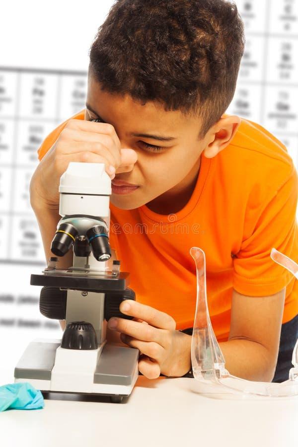 Μαύρο αγόρι που κοιτάζει στο μικροσκόπιο στοκ φωτογραφία με δικαίωμα ελεύθερης χρήσης
