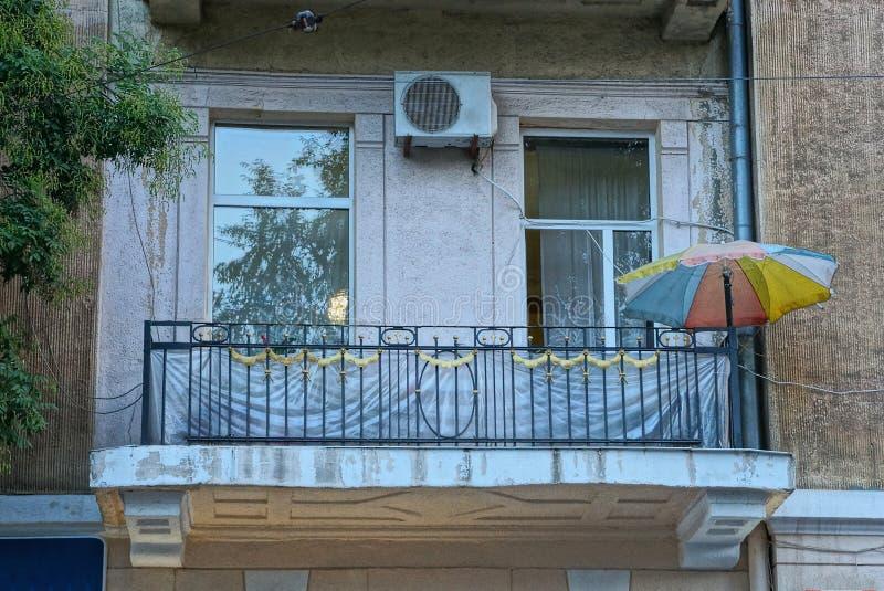 Μαύρο ανοικτό μπαλκόνι σιδήρου σε έναν τοίχο με ένα παράθυρο και μια πόρτα γυαλιού και μια χρωματισμένη ομπρέλα στοκ εικόνα με δικαίωμα ελεύθερης χρήσης