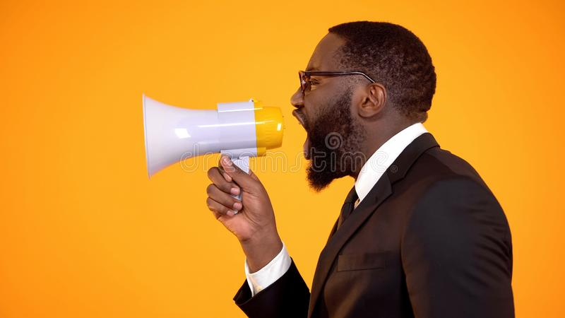 Μαύρο αρσενικό να φωνάξει megaphone, προστασία των ανθρώπινων δικαιωμάτων, ρατσισμός στάσεων, κατάχρηση στοκ εικόνες