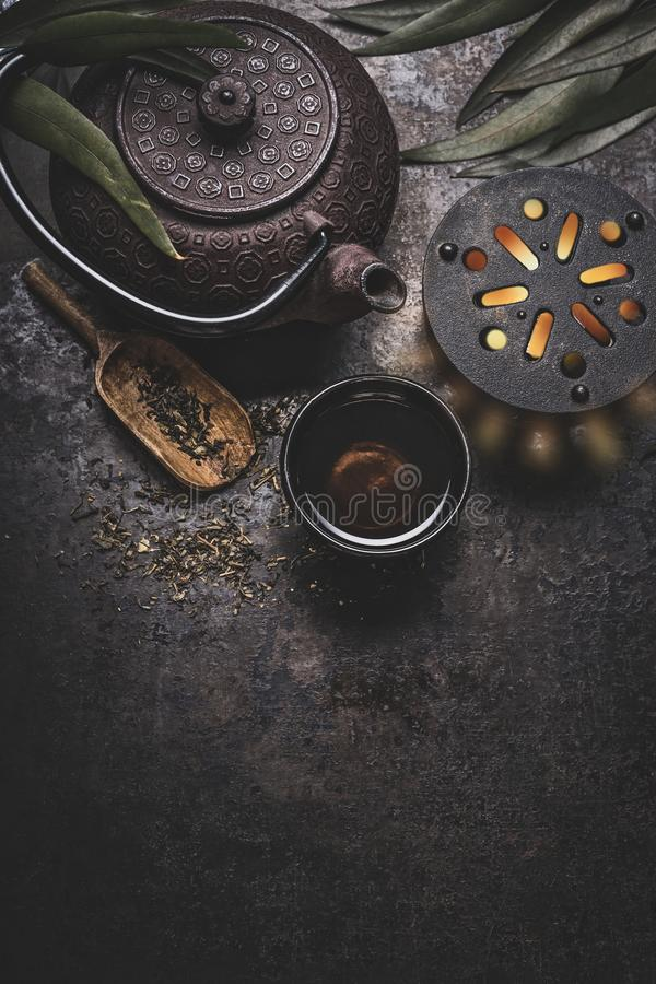 Μαύρο ασιατικό τσάι σιδήρου που τίθεται στο σκοτεινό αγροτικό υπόβαθρο με teapot και τα φρέσκα φύλλα τσαγιού, τοπ άποψη στοκ φωτογραφίες