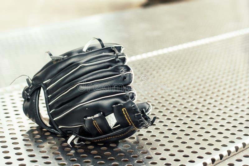 Μαύρο γάντι μπέιζ-μπώλ που τοποθετείται στον πάγκο ανοξείδωτου στοκ εικόνες