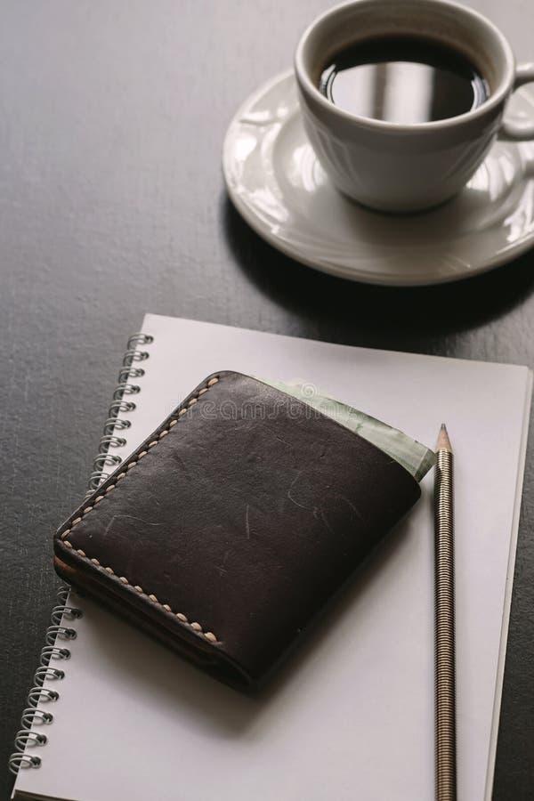 Μαύρο γραφείο με τον καφέ, το πορτοφόλι, το έγγραφο και τη μάνδρα στοκ εικόνες