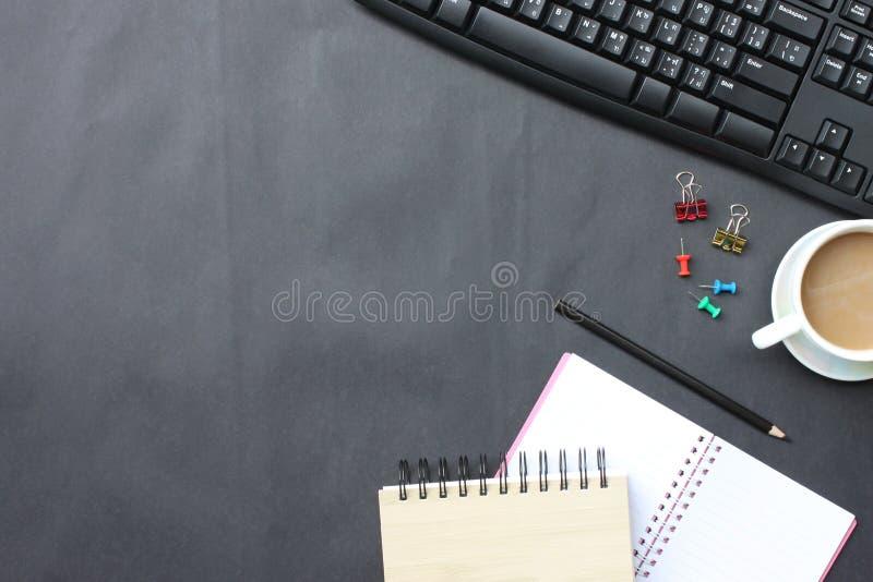 Μαύρο γραφείο με το φλυτζάνι, το πληκτρολόγιο, το σημειωματάριο, και τη μάνδρα καφέ που τοποθετείται στοκ φωτογραφίες