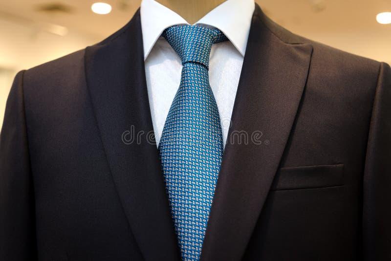 Μαύρο επιχειρησιακό κοστούμι με ένα άσπρο πουκάμισο και με έναν μπλε δεσμό στο σχέδιο στοκ φωτογραφία με δικαίωμα ελεύθερης χρήσης