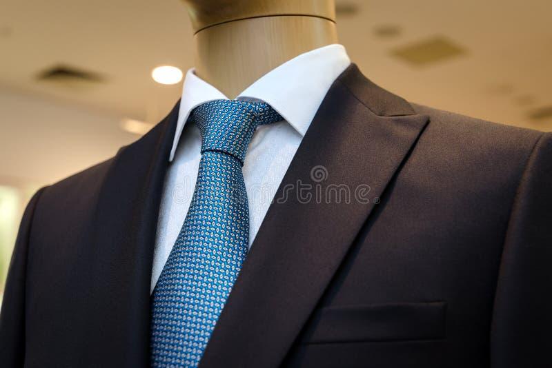 Μαύρο επιχειρησιακό κοστούμι με ένα άσπρο πουκάμισο και με έναν μπλε δεσμό στο σχέδιο στοκ εικόνες