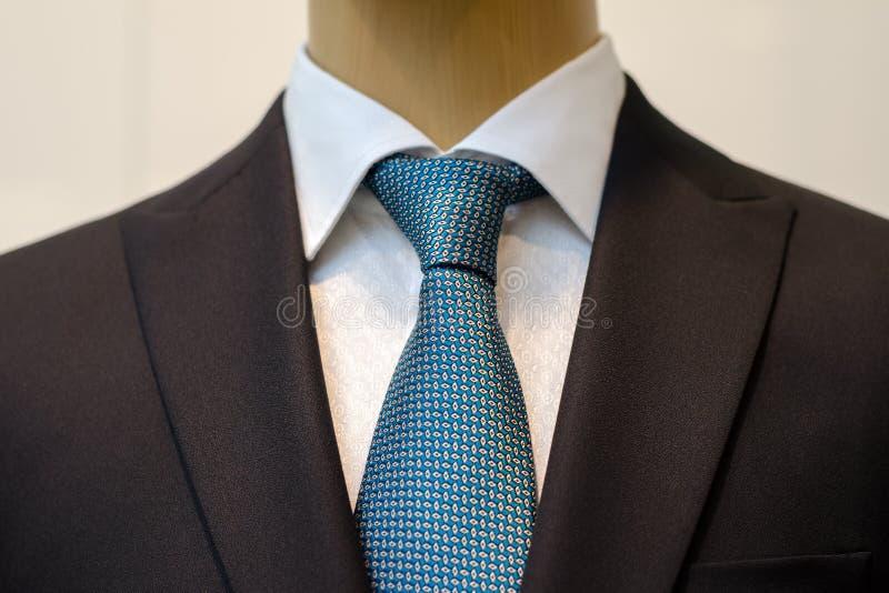 Μαύρο επιχειρησιακό κοστούμι με ένα άσπρο πουκάμισο και με έναν μπλε δεσμό στο σχέδιο στοκ εικόνα με δικαίωμα ελεύθερης χρήσης