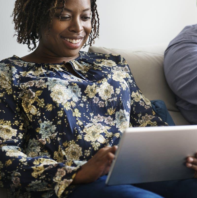 Μαύρο ζεύγος που χαλαρώνει στο σπίτι να χρησιμοποιήσει την ψηφιακή συσκευή στοκ εικόνες