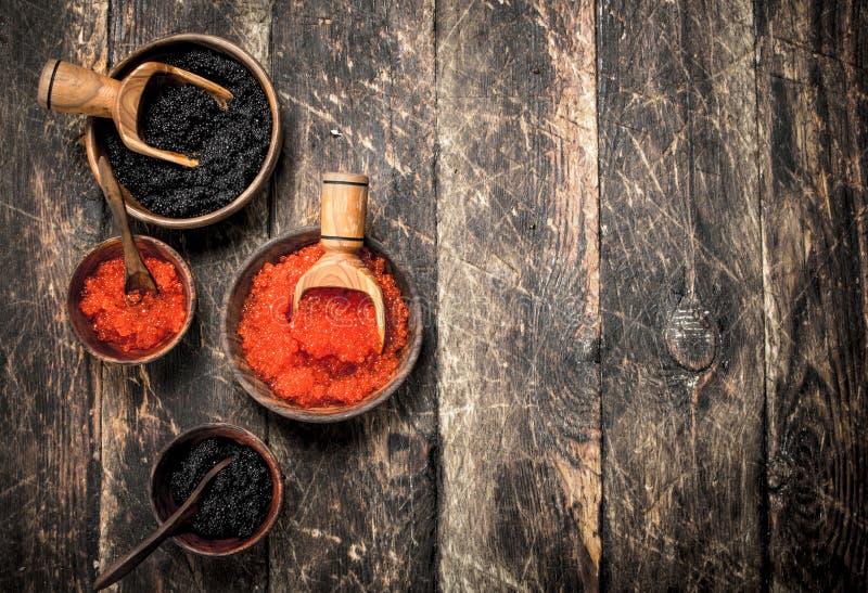 Μαύρο και κόκκινο χαβιάρι στα παλαιά ξύλινα κύπελλα στοκ φωτογραφίες