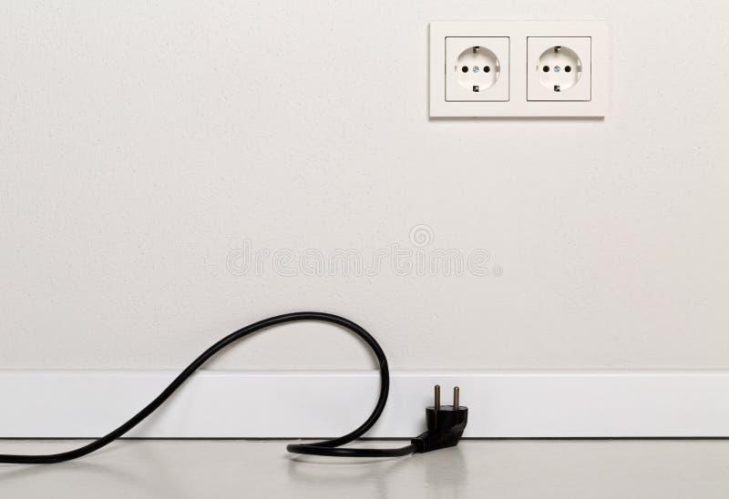 Μαύρο καλώδιο σκοινιού δύναμης που αποσυνδέεται με την ευρωπαϊκή έξοδο τοίχων στο wh στοκ φωτογραφία με δικαίωμα ελεύθερης χρήσης