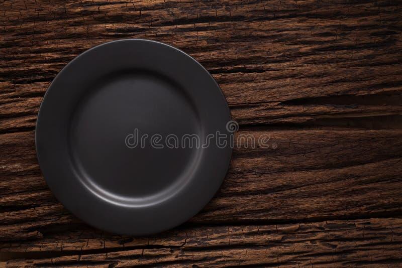 Μαύρο κενό πιάτο στην ξύλινη ζωή επιτραπέζιου υποβάθρου ακόμα στοκ εικόνες με δικαίωμα ελεύθερης χρήσης