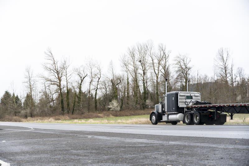 Μαύρο κλασικό μεγάλο ημι φορτηγό εγκαταστάσεων γεώτρησης που μεταφέρ στοκ εικόνες