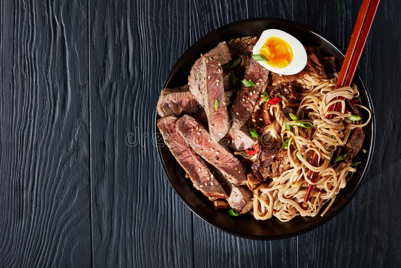 Μαύρο κύπελλο των νουντλς Soba με το βόειο κρέας στοκ εικόνες