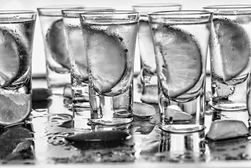 μαύρο λευκό Βότκα κινηματογραφήσεων σε πρώτο πλάνο σε ένα γυαλί με τον πάγο, βότκα ασβέστη, τζιν, τονωτικό, tequila κλείστε επάνω στοκ εικόνα