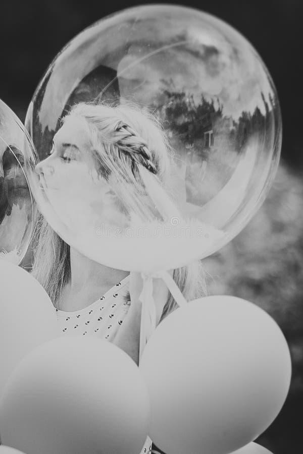 Μαύρο λευκό νέο κορίτσι φωτογραφιών με τα μπαλόνια στο υπόβαθρο φύσης στοκ εικόνες