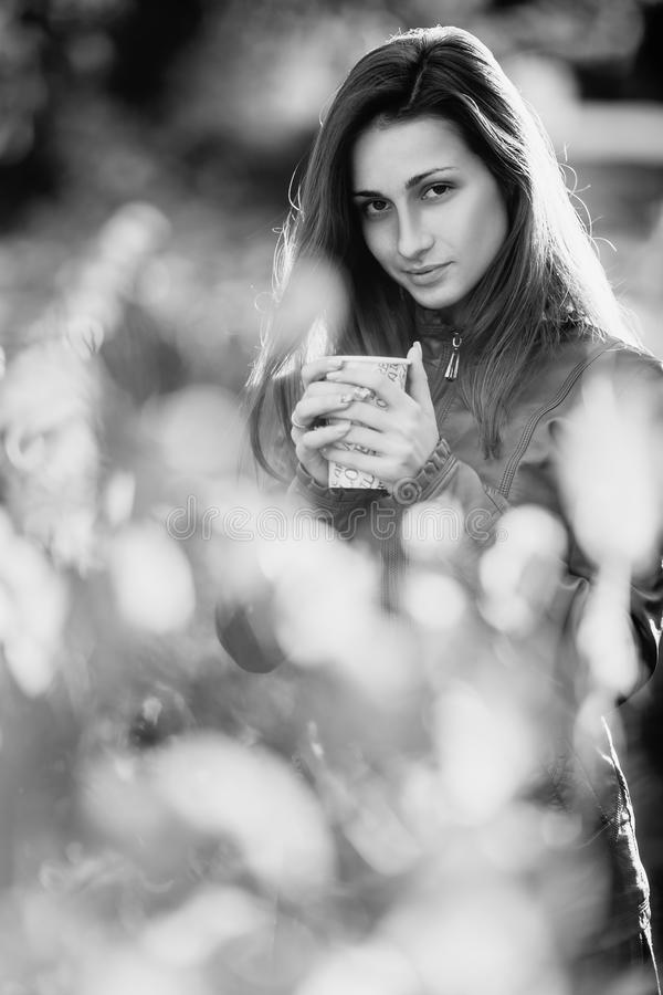 μαύρο λευκό Υπαίθριο πορτρέτο μόδας της πανέμορφης χαμογελώντας γυναίκας στο καφετί σακάκι δέρματος με το φλυτζάνι του coffe Μοντ στοκ εικόνα με δικαίωμα ελεύθερης χρήσης