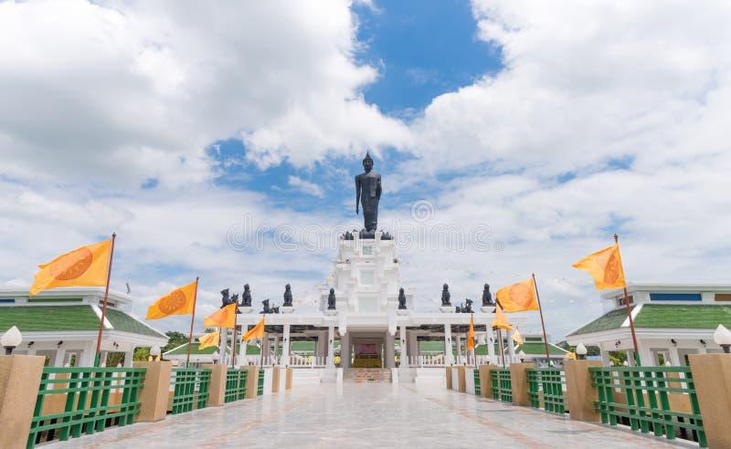 Μαύρο μεγάλο άγαλμα του Βούδα με άσπρους νεφελώδη και το μπλε ουρανό στοκ φωτογραφία