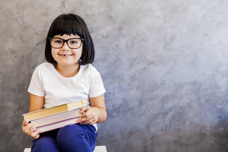 Μαύρο μικρό κορίτσι τρίχας με τα γυαλιά που κρατά τα βιβλία από τον τοίχο στοκ φωτογραφία