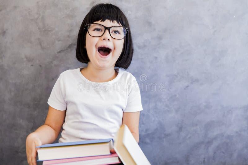 Μαύρο μικρό κορίτσι τρίχας με τα γυαλιά που κρατά τα βιβλία από τον τοίχο στοκ εικόνες