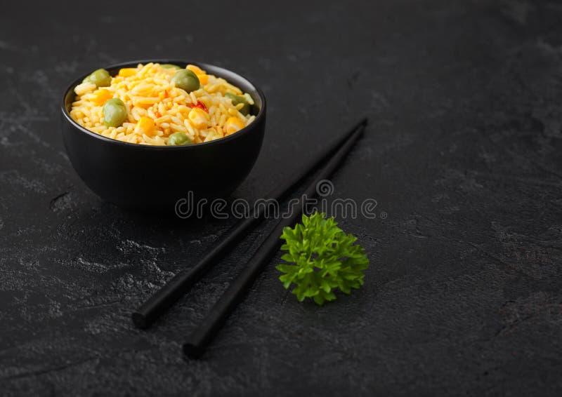 Μαύρο μπολ με βραστό οργανικό ρύζι basmati με μαύρα ξυλάκια σε μαύρο πέτρινο φόντο Κίτρινο καλαμπόκι και πράσινα μπιζέλια στοκ εικόνες με δικαίωμα ελεύθερης χρήσης