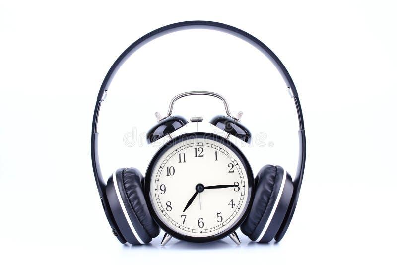 Μαύρο ξυπνητήρι με το ακουστικό που απομονώνεται στο άσπρο υπόβαθρο στοκ φωτογραφία