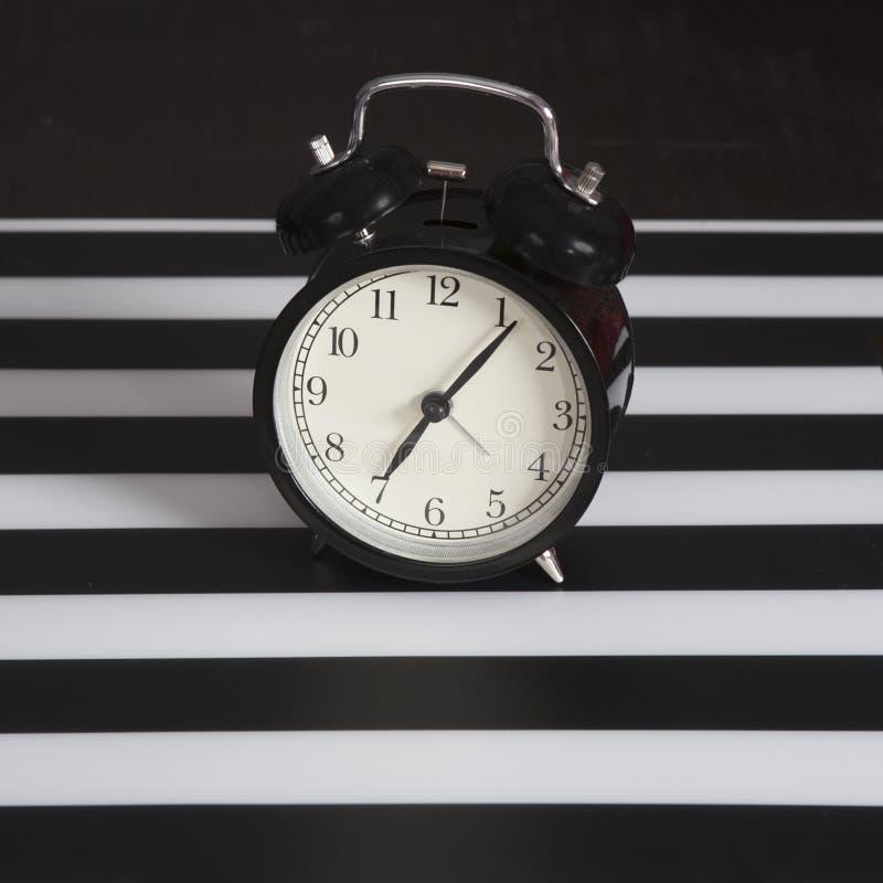 Μαύρο ξυπνητήρι σε μια γραπτή ριγωτή πετσέτα που παρουσιάζει ρολόι 7 ο ` σε έναν πίνακα πλευρών στοκ εικόνες με δικαίωμα ελεύθερης χρήσης