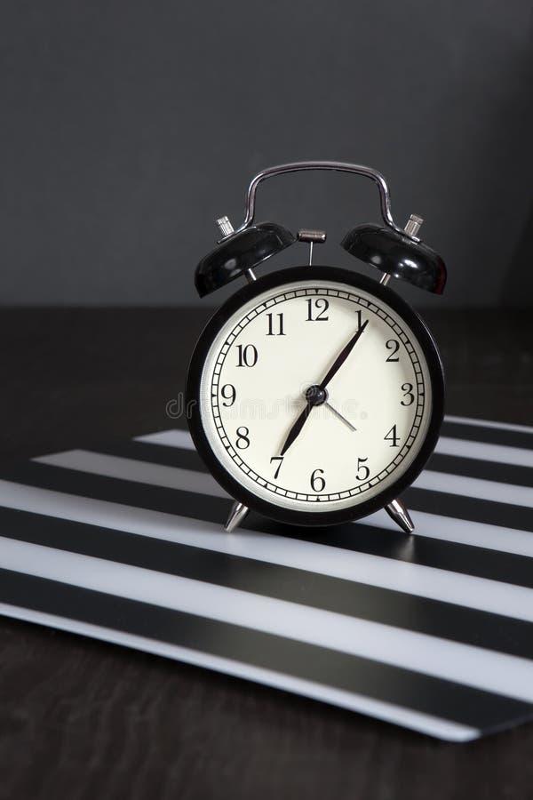 Μαύρο ξυπνητήρι σε μια γραπτή ριγωτή πετσέτα που παρουσιάζει ρολόι 7 ο ` σε έναν πίνακα πλευρών στοκ εικόνες