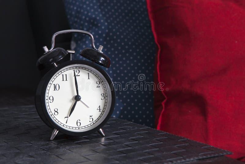 Μαύρο ξυπνητήρι σε μια γραπτή ριγωτή πετσέτα που παρουσιάζει 7 o& x27 ρολόι σε έναν πίνακα πλευρών στοκ εικόνα