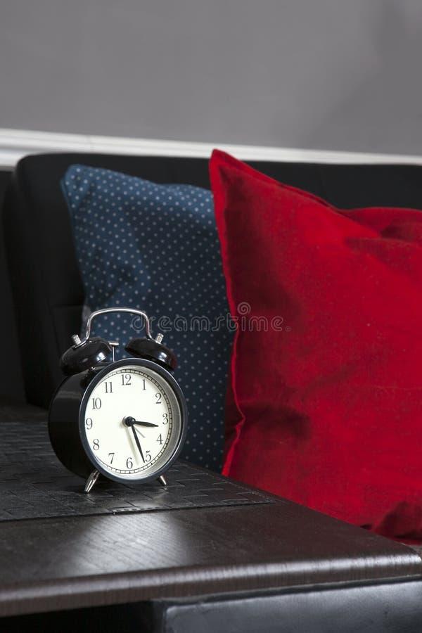 Μαύρο ξυπνητήρι σε μια γραπτή ριγωτή πετσέτα που παρουσιάζει 7 o& x27 ρολόι σε έναν πίνακα πλευρών στοκ φωτογραφία