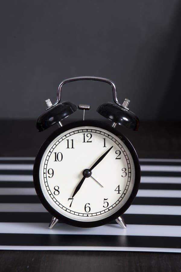 Μαύρο ξυπνητήρι σε μια γραπτή ριγωτή πετσέτα που παρουσιάζει 7 o& x27 ρολόι σε έναν πίνακα πλευρών στοκ φωτογραφία με δικαίωμα ελεύθερης χρήσης