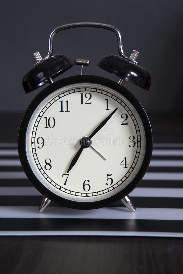 Μαύρο ξυπνητήρι σε μια γραπτή ριγωτή πετσέτα που παρουσιάζει 7 o& x27 ρολόι σε έναν πίνακα πλευρών στοκ εικόνες με δικαίωμα ελεύθερης χρήσης