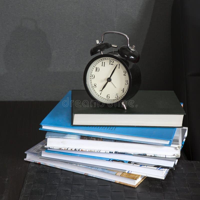 Μαύρο ξυπνητήρι σε μια γραπτή ριγωτή πετσέτα που παρουσιάζει 7 o& x27 ρολόι σε έναν πίνακα πλευρών στοκ εικόνα με δικαίωμα ελεύθερης χρήσης
