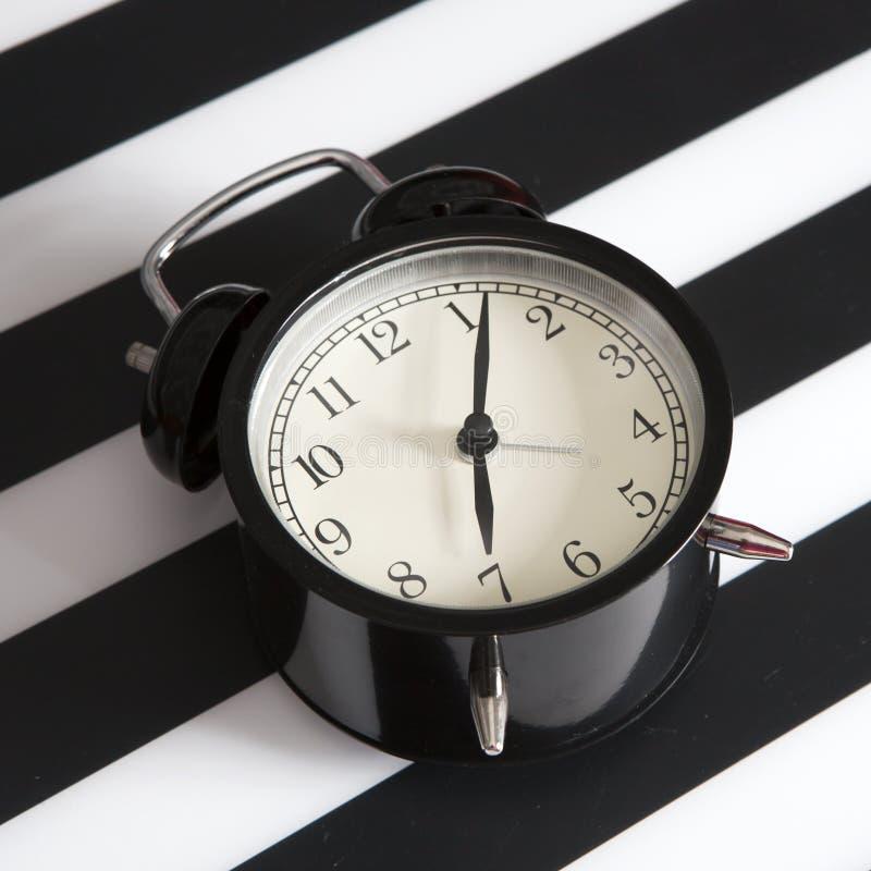 Μαύρο ξυπνητήρι σε μια γραπτή ριγωτή πετσέτα που παρουσιάζει 7 o& x27 ρολόι σε έναν πίνακα πλευρών στοκ εικόνες