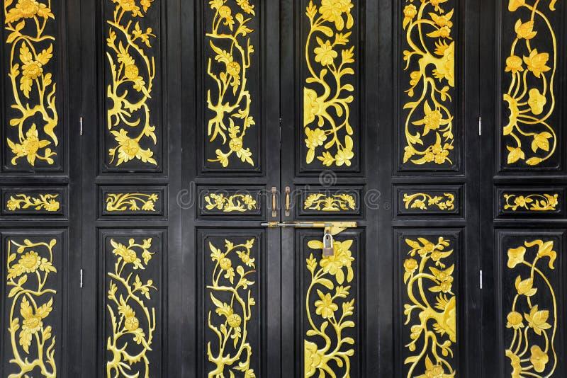 Μαύρο ξύλινο κινεζικό εκλεκτής ποιότητας ύφος που χαράζεται δίπλωμα των πορτών στοκ εικόνες