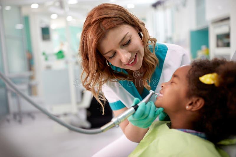 Μαύρο παιδί με το θηλυκό οδοντίατρο στην οδοντική κλινική στοκ φωτογραφίες