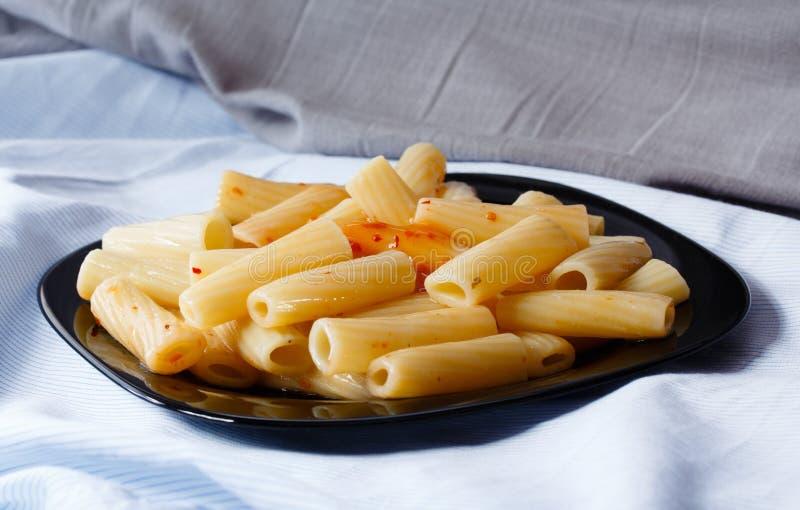 Μαύρο πιάτο των ζυμαρικών με τη σάλτσα στοκ εικόνες