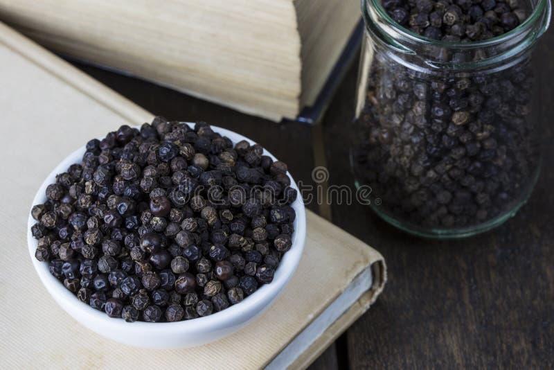 Μαύρο πιπέρι σωρών στο άσπρο βάζο κύπελλων και γυαλιού στο παλαιό ξύλινο tabl στοκ φωτογραφία με δικαίωμα ελεύθερης χρήσης