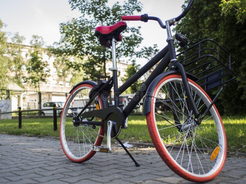 μαύρο ποδήλατο πόλεων με τις κόκκινες ρόδες στοκ φωτογραφία με δικαίωμα ελεύθερης χρήσης