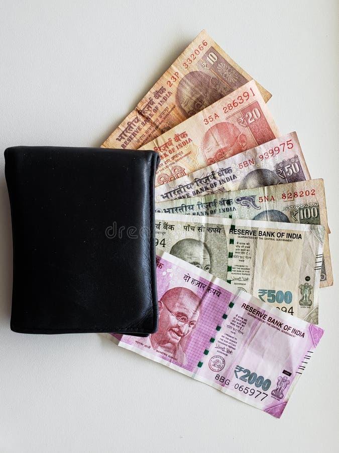 μαύρο πορτοφόλι δέρματος και ινδικά τραπεζογραμμάτια των διαφορετικών μετονομασιών στοκ εικόνα