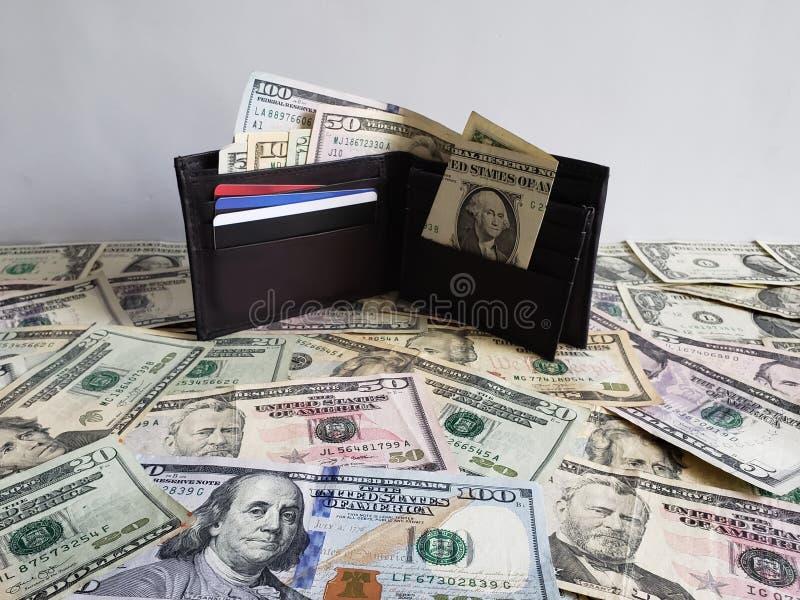 μαύρο πορτοφόλι δέρματος με τους αμερικανικούς λογαριασμούς δολαρίων των διαφορετικών μετονομασιών στοκ φωτογραφία