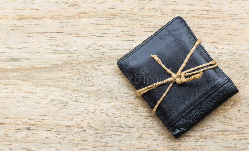 Μαύρο πορτοφόλι δέρματος με τα σχοινιά στο ξύλινο υπόβαθρο στοκ εικόνες