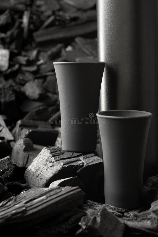 Μαύρο πυροβοληθε'ν γυαλί δύο μεταλλινών Στο υπόβαθρο ξυλάνθρακα Μαύρη έκδοση δημιουργικός Πιείτε Ευθυμίες Πρότυπο διάστημα αντιγρ στοκ εικόνες