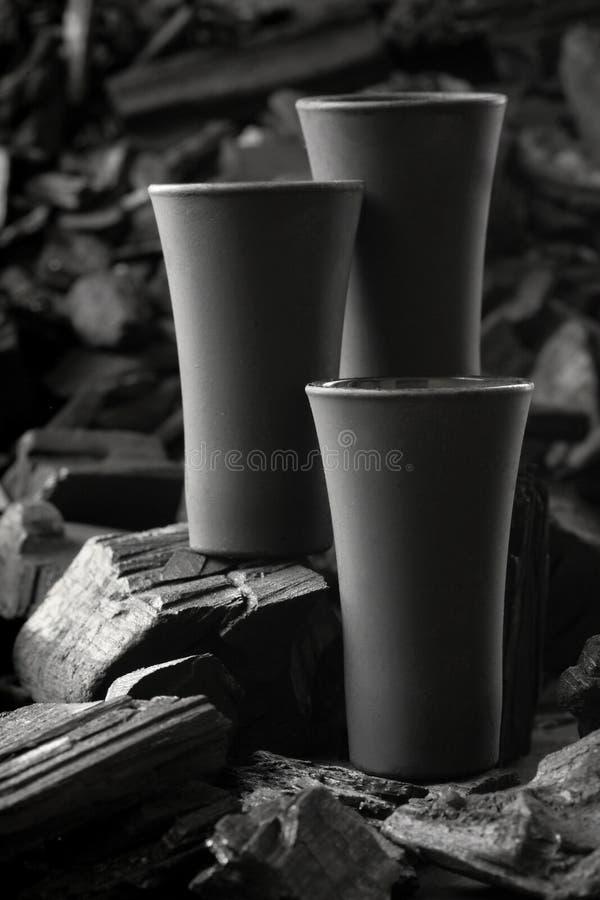 Μαύρο πυροβοληθε'ν γυαλί τριών μεταλλινών Στο υπόβαθρο ξυλάνθρακα Μαύρη έκδοση δημιουργικός Πιείτε Ευθυμίες Πρότυπο διάστημα αντι στοκ εικόνα